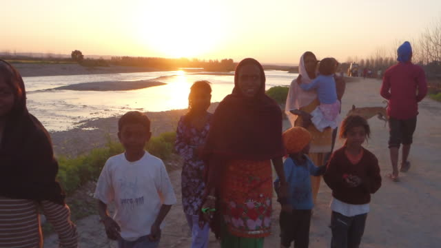 family walks in the sunset by the river in rural inda. - punjab india stock videos and b-roll footage