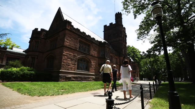 Family walks near a historic stone building on Princeton University campus