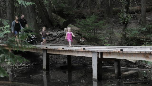 family walks on dock side veiw - familie mit drei kindern stock-videos und b-roll-filmmaterial