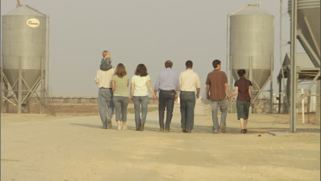 a family walks past a silo and chicken coop. - chicken coop stock videos and b-roll footage