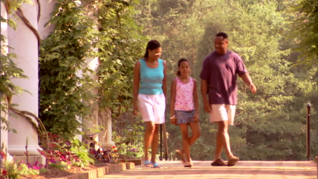 stockvideo's en b-roll-footage met a family walks toward the viewer on a brick pathway among flower gardens. - tuinpad
