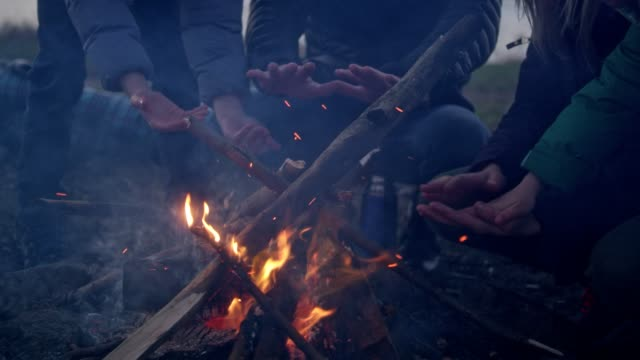 family warming hands in the bonfire. winter fun. riverside in the city - campfire stock videos & royalty-free footage