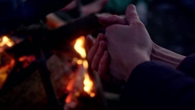 vídeos y material grabado en eventos de stock de familia de calentar las manos en la hoguera. diversión de invierno. riverside de la ciudad - abrigo de invierno