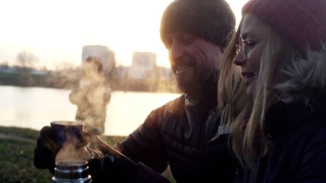 家族は、たき火でウォーミング アップ。冬の楽しみ。リバーサイド市 - ウィンターコート点の映像素材/bロール