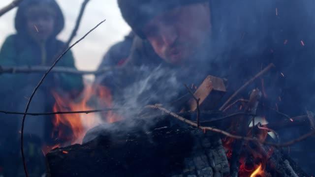 family warming up at bonfire. winter fun. riverside in the city - cappotto invernale video stock e b–roll