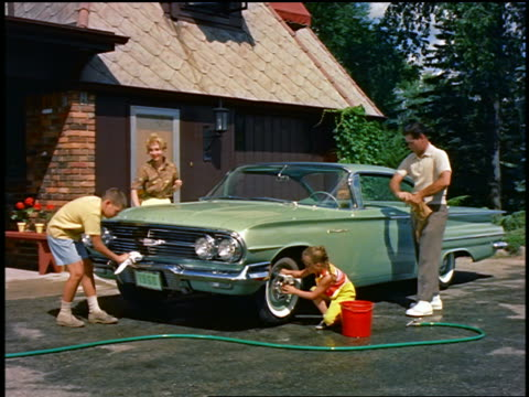 vídeos de stock e filmes b-roll de 1959 family washing chevrolet impala in driveway - 1950 1959