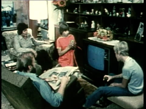 family watches television in a living room. - living room stock videos & royalty-free footage