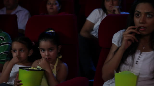 Family watching a movie in cinema hall