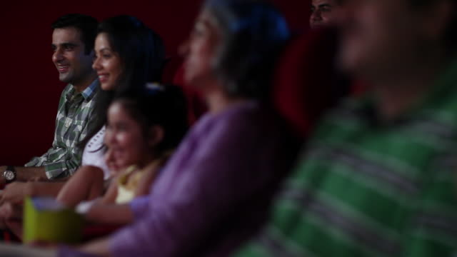 family watching a movie in cinema hall  - focus on background stock videos and b-roll footage