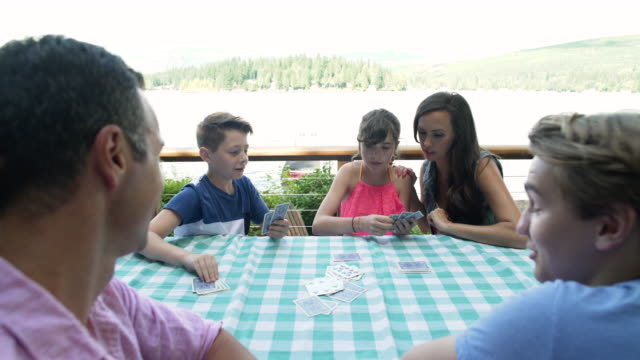family watching brother and sister playing game of cards at table, lake connaught, washington, usa. - familie mit drei kindern stock-videos und b-roll-filmmaterial