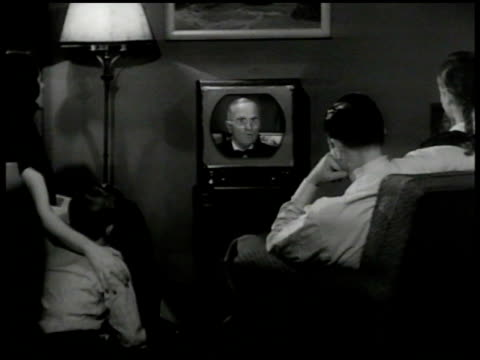 Family watching Pres Harry Truman speaking on old television set 'buy only what you really need cannot do w/o do not pile up inventories' MS Daughter...