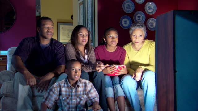 family watching television and cheering - andere clips dieser aufnahmen anzeigen 1282 stock-videos und b-roll-filmmaterial
