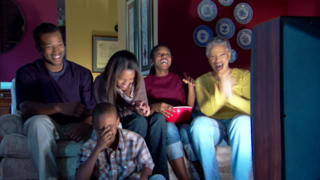 family watching television and laughing - andere clips dieser aufnahmen anzeigen 1282 stock-videos und b-roll-filmmaterial