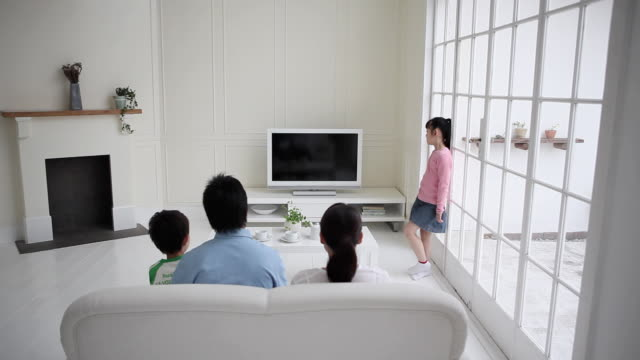 WS Family watching TV in living room, girl (8-9) standing by French door / Setagaya, Tokyo, Japan