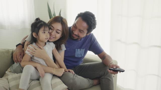 vidéos et rushes de famille regardant la tv sur le sofa à la maison. - routine