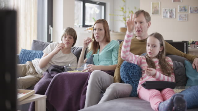 'Family watching TV, talking and eating popcorn'