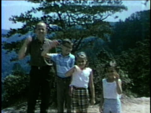 vidéos et rushes de a family waves as they stand in front of a tree. - 1960