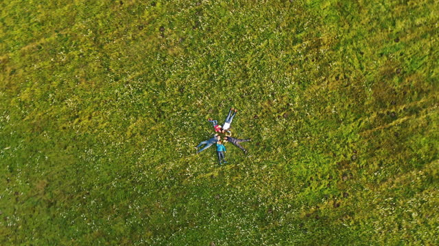 aerial family waving at the camera while lying in a circle in the grass - family with three children stock videos & royalty-free footage