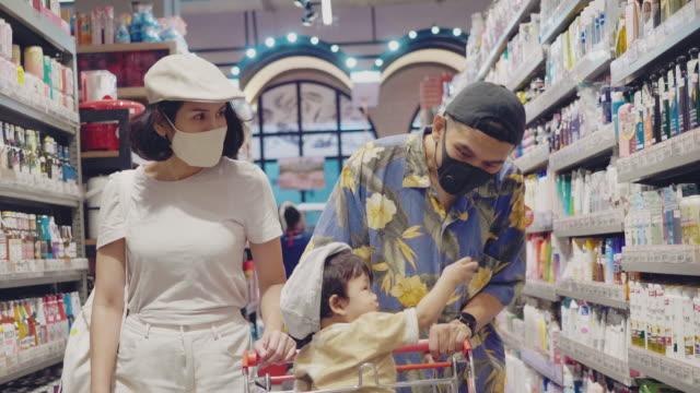 vidéos et rushes de famille utilisant un magasinage protecteur de masque de visage dans le supermarché. - tous types de crises