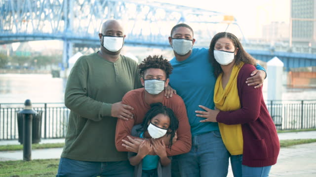family wearing face masks during covid-19 pandemic - waist up stock videos & royalty-free footage