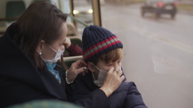 family wearing protective medical mask in bus - pollution mask stock videos & royalty-free footage