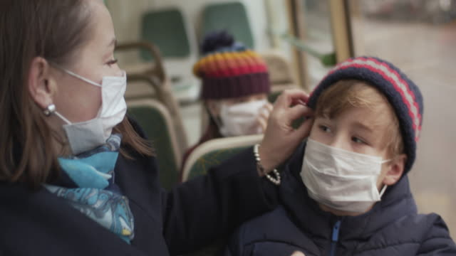 familie trägt medizinische schutzmaske im bus - bus stock-videos und b-roll-filmmaterial
