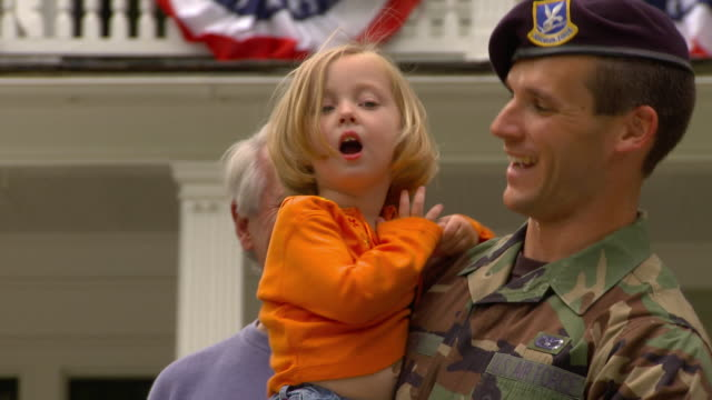 CU Family welcoming home and embracing soldier in front of suburban home decorated with bunting / Richmond, Virginia