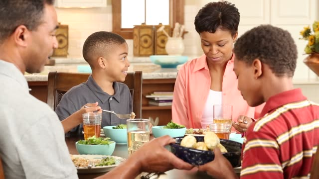 ms family with 2 children in kitchen eating dinner - middle class stock videos & royalty-free footage