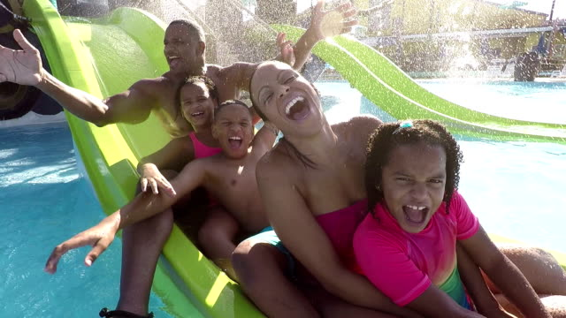 family with 3 children waving on slide at water park - water slide stock videos & royalty-free footage