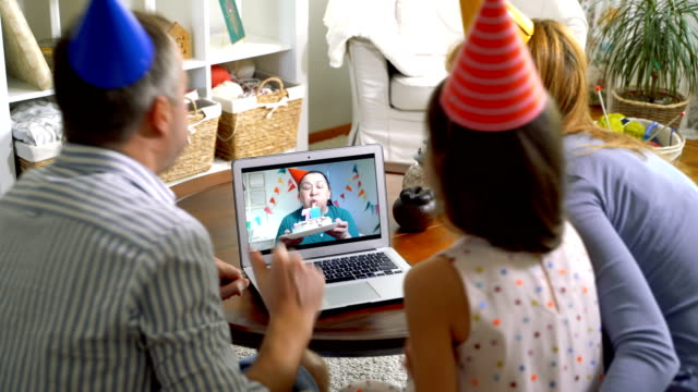 A family with a child congratulating a grandmother on her birthday using a video call.
