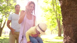 Family with a little girl swinging happily in the park