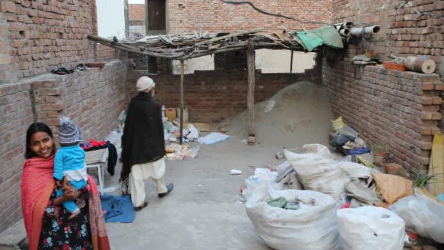 family with baby in a simple backyard where you can see bricks - punjab pakistan bildbanksvideor och videomaterial från bakom kulisserna