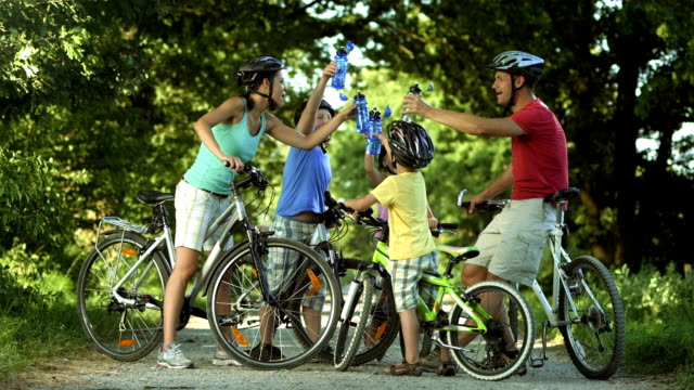 hd: family with bicycles taking a drinking break - cycling helmet stock videos & royalty-free footage