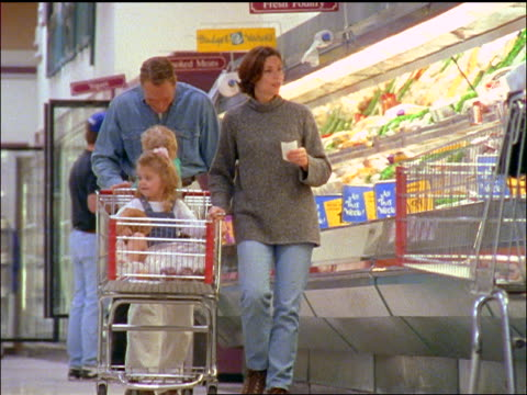 Family with children sitting in cart shopping in supermarket + walking towards camera