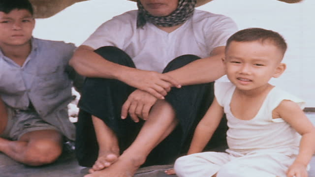 pan family with children sitting on deck of sampan smiling / vietnam - sampan stock videos & royalty-free footage