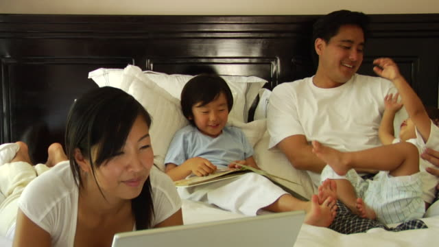 zo, cu, family with daughter (18-23 months) and son (6-7) relaxing in bed - 18 23 months stock videos & royalty-free footage