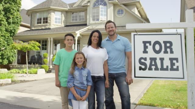 """familie mit """"für sale real estate sign - zweistöckiges wohnhaus stock-videos und b-roll-filmmaterial"""