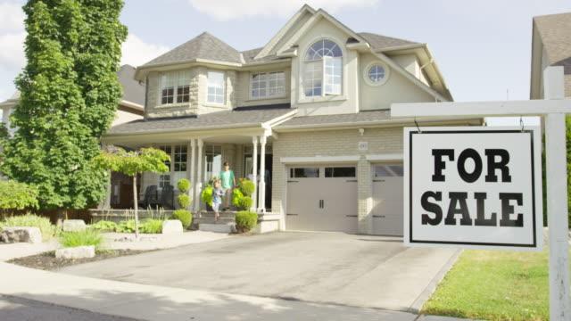 """familie mit """"für sale real estate sign - immobilienschild stock-videos und b-roll-filmmaterial"""