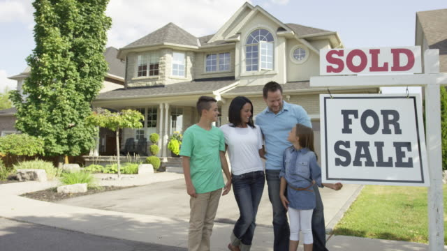 "family with ""for sale, sold"" real estate sign - selling stock videos and b-roll footage"
