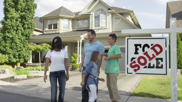 """family with """"for sale, sold"""" real estate sign - selling stock videos and b-roll footage"""