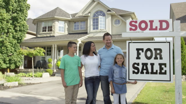 "family with ""for sale, sold"" real estate sign - selling stock videos & royalty-free footage"