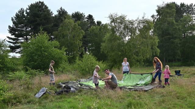vídeos de stock e filmes b-roll de family with four children setting up tent on camping trip - família com quatro filhos