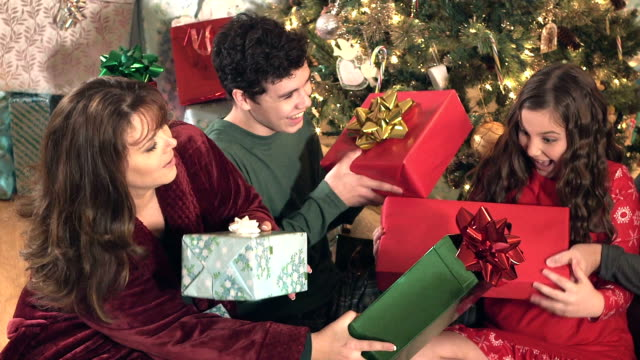family with gifts by the christmas tree - gift stock videos & royalty-free footage