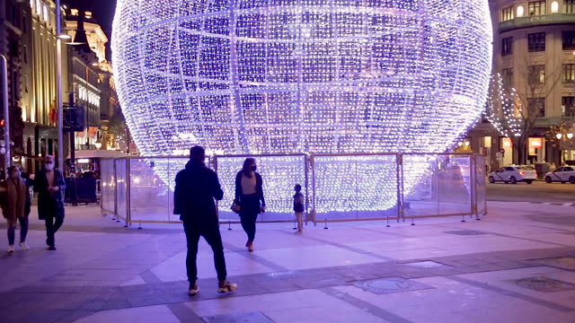 family with one kid take selfies with a giant ball made of 43,000 light bulbs shining behind them, at the intersection of alcalá and gran vía... - マドリード グランヴィア通り点の映像素材/bロール