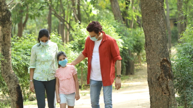 family with protective face mask at park - care stock videos & royalty-free footage