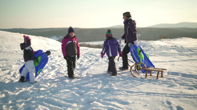 stockvideo's en b-roll-footage met family with sleds during winter holiday - familie met drie kinderen
