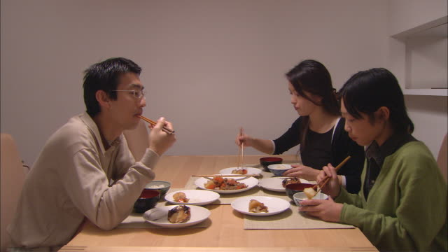 CU, Family with son (10-11) having traditionally Japanese dinner