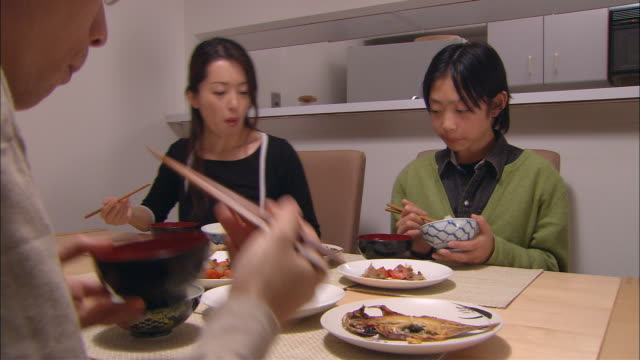 cu, family with son (10-11) having traditionally japanese dinner - giapponese video stock e b–roll