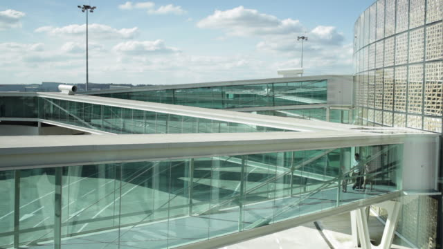 WS Family with son (8-9) walking along glass walkway away from airport building / Toulouse, Haute-Garonne, France