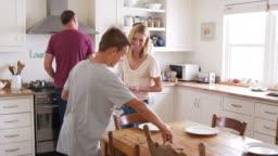 Family With Teenage Children Preparing Breakfast In Kitchen